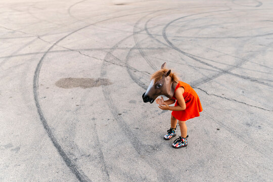 Little girl with a horse's head and a red dress, standing on asphalt with tire tracks