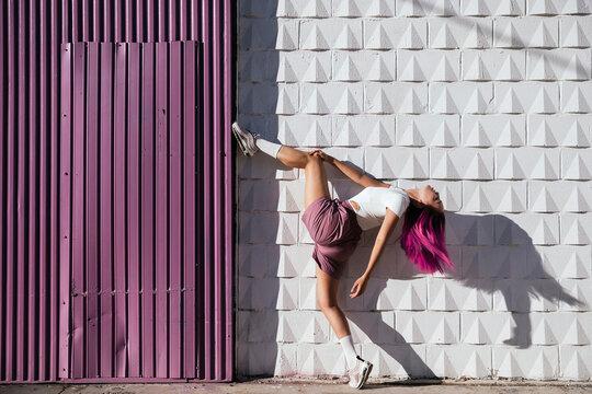 Young female dancer lifting leg at purple wall