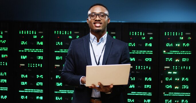 Portrait of joyful African American handsome male IT technician specialist in glasses standing in server room checking data security of processors in storage, tapping on laptop and smiling at camera
