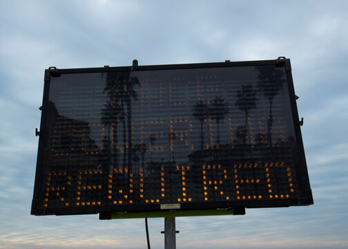 Palm trees are reflected in a warning sign on the beach as new stay-at-home orders begin in Southern California