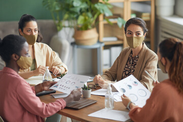 High angle view at multi-ethnic group of young businesswomen wearing masks during meeting in office, copy space Wall mural