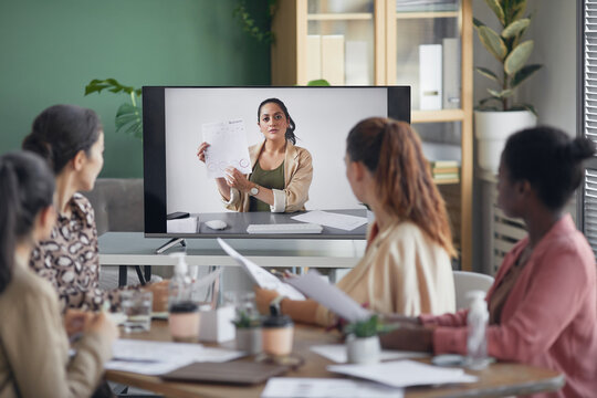 Portrait of businesswoman on computer screen talking to team and showing document during online business meeting in office, copy space