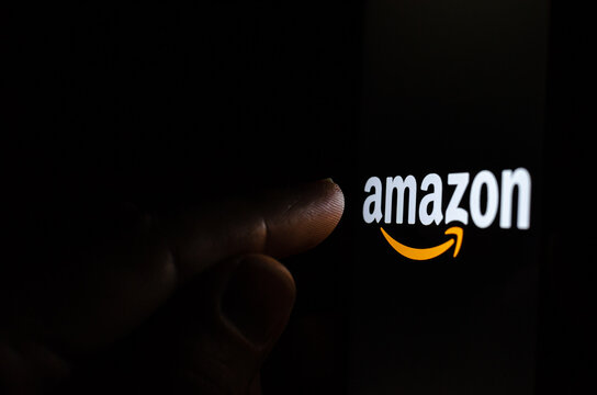 Amazon logo on a smartphone screen in a dark room and a finger pointing at it.