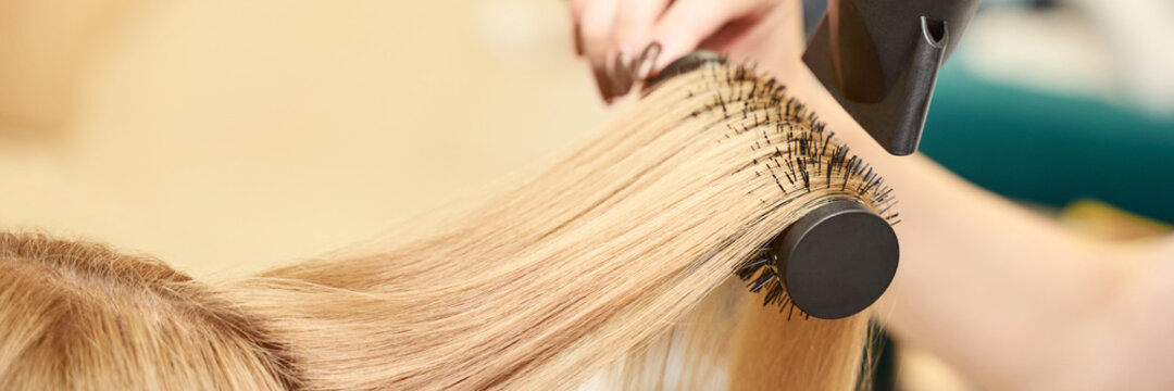 Repair long hair procedure. Haircut at salon. Woman hairstyle. Master hand with brush and fan. Adult female person. Closeup view. Studio equipment. Lady preparation. Blonde dry. Copyspace