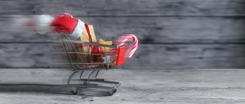 Fast small shopping cart with presents, christmas decoration, sweets and Santa Claus hat is driving on rustic wooden planks for last minute online gifts, panoramic format with copy space, motion blur