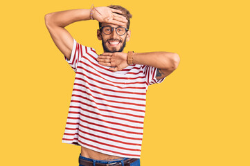 Handsome blond man with beard wearing casual clothes and glasses smiling cheerful playing peek a boo with hands showing face. surprised and exited Wall mural