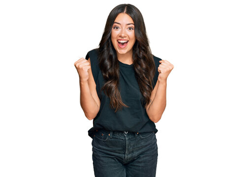 Beautiful brunette young woman wearing black shirt celebrating surprised and amazed for success with arms raised and open eyes. winner concept.