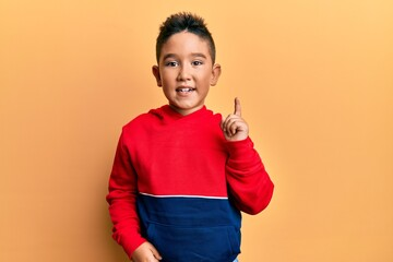 Little boy hispanic kid wearing casual sweatshirt pointing finger up with successful idea. exited and happy. number one. Wall mural