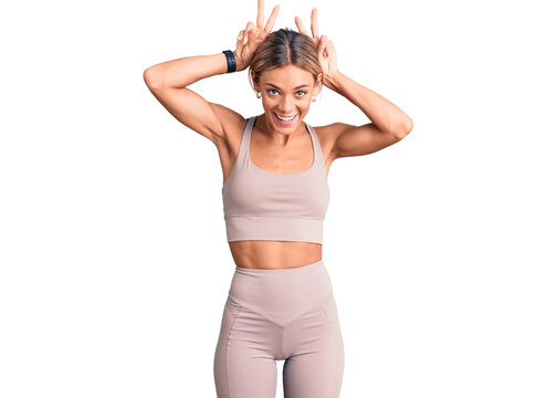 Beautiful caucasian woman wearing sportswear posing funny and crazy with fingers on head as bunny ears, smiling cheerful