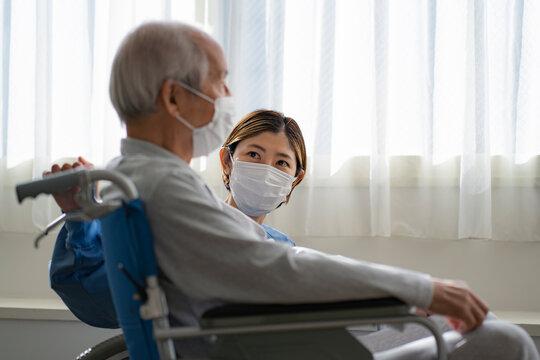 マスクをつけて車椅子に座る日本人シニア男性と看護師