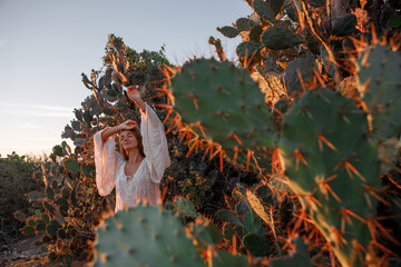 Young woman dressed in white dress and straw hat standing among cactuses