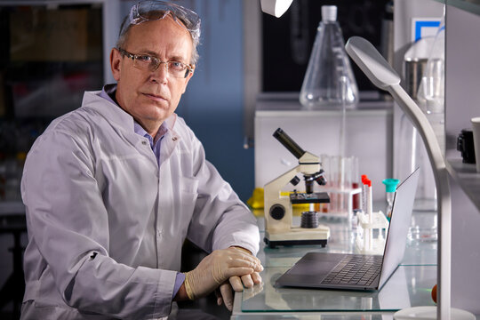 senior scientist man in white dress coat sitting in laboratory at work place, successful serious face and feeling expression. caucasian microbiologist make research