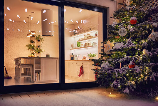 cozy apartment with sliding doors, and decorated christmas tree on the patio at snowy winter night