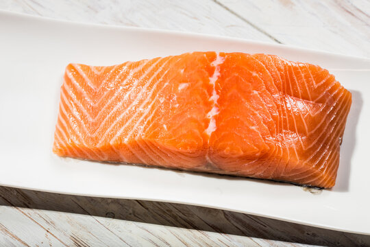 raw salmon fillet over wooden white table