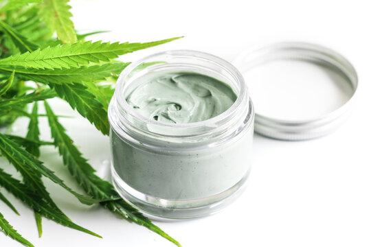 Green cannabis plant and jar with a moisturizing cream