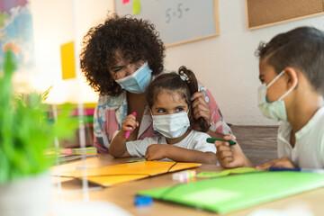 Teacher with children wearing face mask in preschool classroom during corona virus pandemic -...