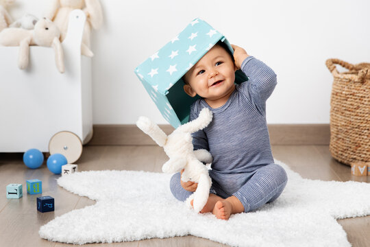 Funny baby in playroom with basket on head