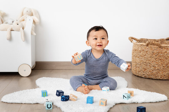 Smiling baby playing with alphabet blocks in playroom