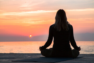middle-aged woman is meditating at lotus asana at sunrise on the beac