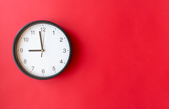 Round wall clock on red surface showing 9 o'clock, layout, top view, place for text.
