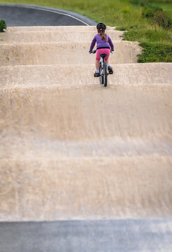Young girl riding on her bicycle on a dirt race track