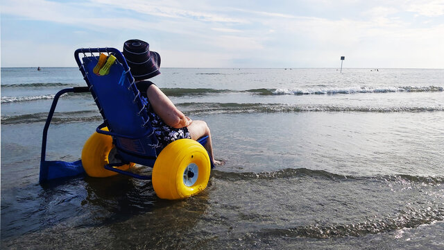 disabled senior lady on a special wheelchair to the beach