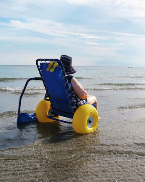 disabled senior lady ona special wheelchair to the beach