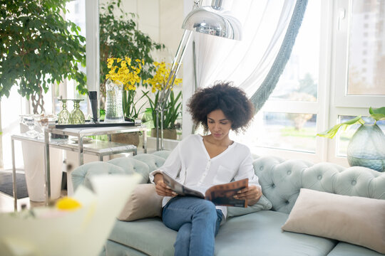 Smiling young woman reading magazine in cozy room