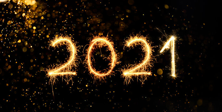 Happy New Year 2020. Number 2020 written sparkling sparklers isolated on back with bokeh background