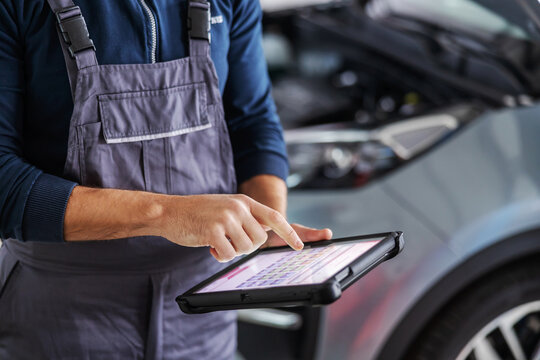Mechanic using tablet for diagnosing a car issue. Garage of car salon interior.
