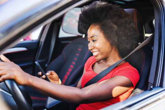 Young attractive african woman driving her car and looking at smart phone.