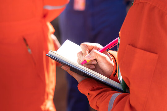 Writing or take note action of supervisor during perform safety audit at working site location. Close-up and selective focus at person hand.