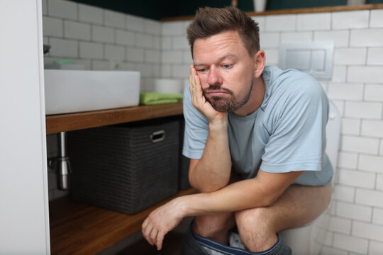 Man sit on toilet with constipation and wait for laxative to take effect. Digestive system disease and treatment.