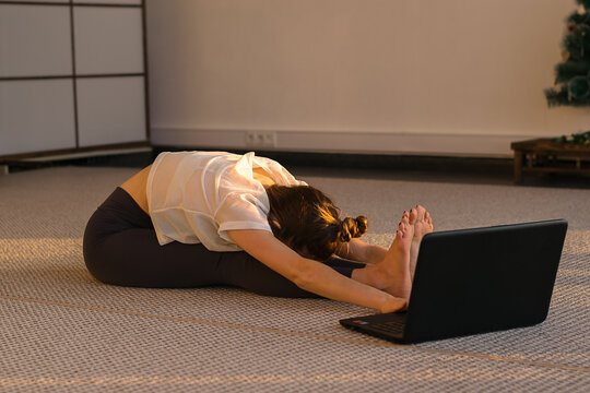 Young woman does yoga online at home in front of a laptop webcam.Girl doing paschimottanasana exercise, seated forward bend pose.Yoga online in the covid pandemic.