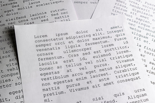 lorem ipsum dolor sit amet concept. selective focus photo of paper sheets with publishing and graphic design placeholder text on them.