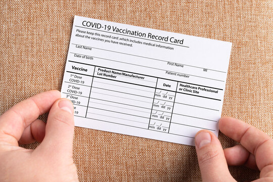 The coronavirus vaccination card is held in the hands. The concept of defeating Covid-19
