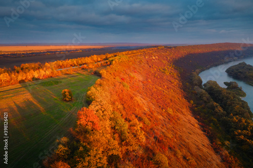 Wall mural Beautiful top view of winding river in sunset. Scenic image of drone photography.