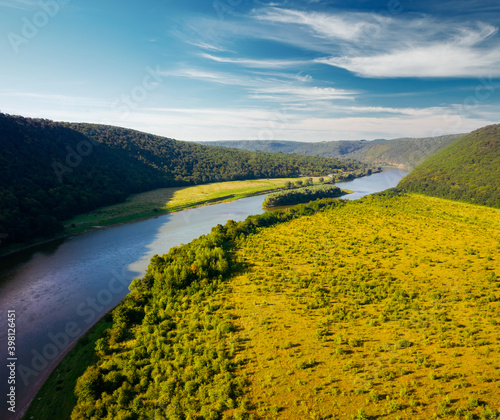 Wall mural Attractive view from a drone flying over the sinuous river.