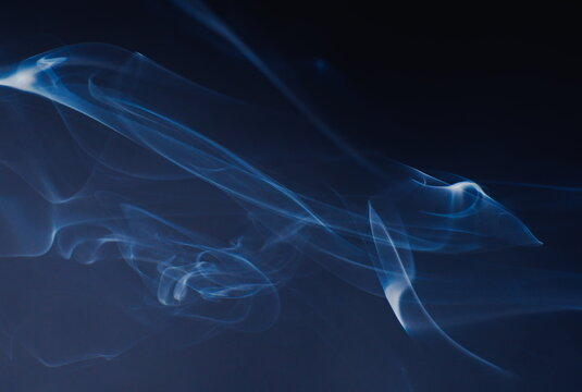 Abstract photographs of billowing smoke swirling and moving in the air.