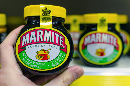 Stone, Staffordshire / United Kingdom - October 27 2019: Marmite jar hold in a hand next to supermarket shelf with the other jars. Traditional English product made of yeast.