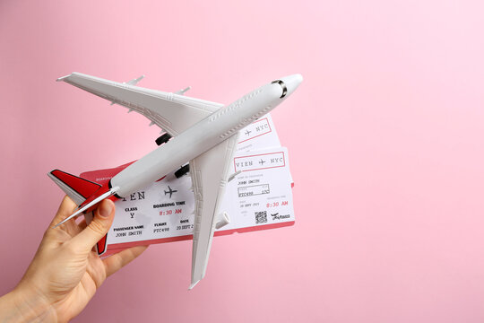 Woman holding toy airplane and tickets on pink background, closeup
