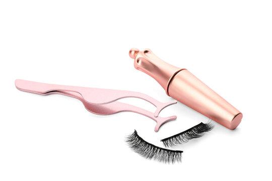 Magnetic eyelashes, eyeliner and tweezers on white background
