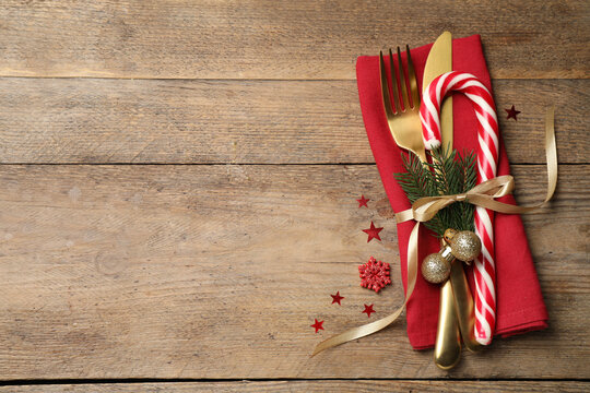 Cutlery set and festive decor on wooden table, flat lay with space for text. Christmas celebration
