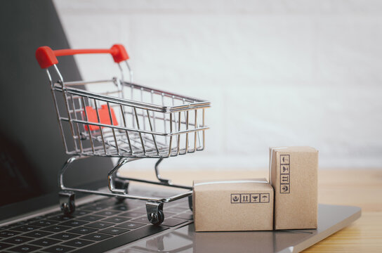 Brown paper boxs and cart with laptop on wood table in office background.Easy shopping with finger tips for consumers.Online shopping and delivery service concept.