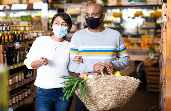 Positive hispanic couple in protective face masks shopping in grocery store during pandemic, carrying wicker bag full of food goods. Concept of new life reality and precautions
