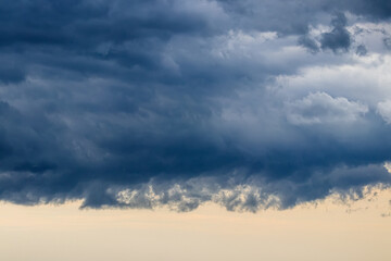 Dark blue heavy storm clouds before a thunderstorm or hurricane. Dramatic clouds in overcast weather. Fotobehang