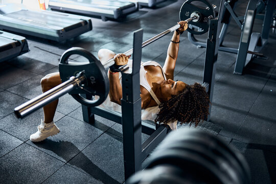 Calm athletic lady performing the bench press