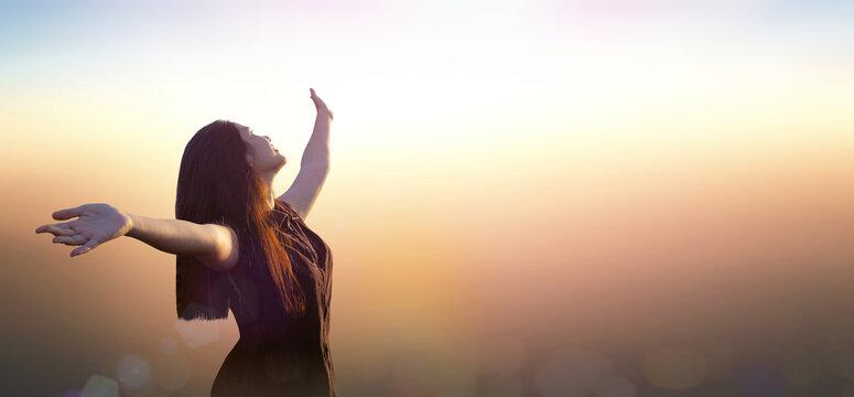 Worship God concept: Silhouette happy Asian girl on blurred mountain sunrise background. Ai Yerweng, Bethong, Yala, Thailand, Asia