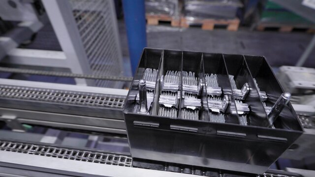 Automatic line for the assembly of car batteries. The black batteries move and collect on the conveyor belt.
