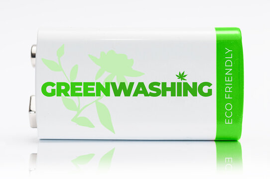 9 volt green and white battery with the word Greenwashing printed on it. Greenwashing is a communication technique aimed at building a false image of a company in terms of environmental impact.